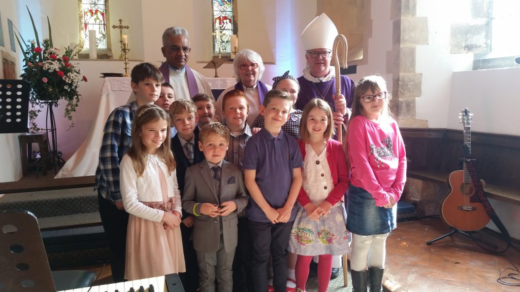 Rt Rev David Court (Biship of Grimsby) with the young children now sharing in our Church Family Communion