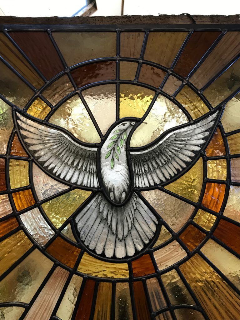 An illustration of a similar dove in a church window created by the artist